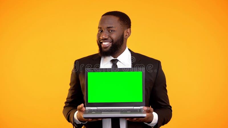 Hombre de negocios afroamericano que sostiene el ordenador port?til prekeyed y que sonr?e, plantilla del anuncio fotos de archivo