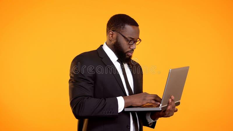 Hombre de negocios afroamericano que trabaja en el ordenador port?til, crecimiento de la carrera, desarrollo de proyecto foto de archivo libre de regalías