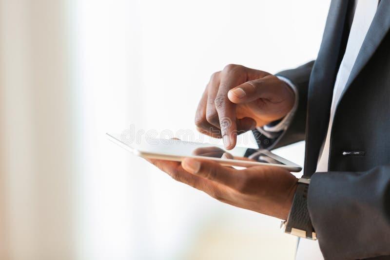 Hombre de negocios afroamericano que usa una tableta táctil sobre blanco imagen de archivo