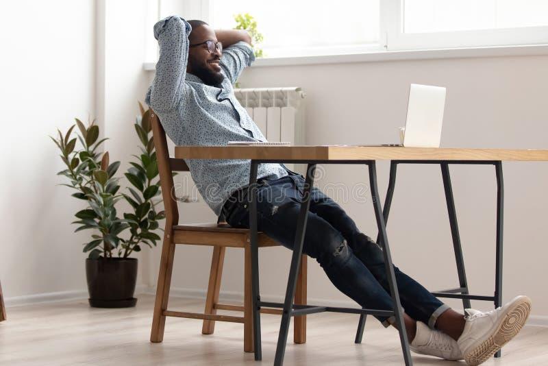 Hombre de negocios afroamericano relajado que se enfría en trabajo acabado sitio de la oficina imágenes de archivo libres de regalías