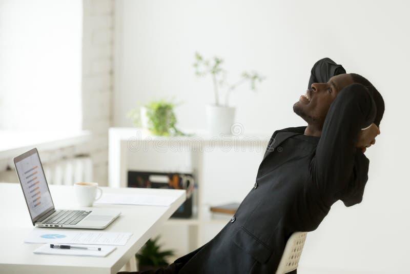 Hombre de negocios afroamericano relajado satisfecho en el traje que siente h imágenes de archivo libres de regalías