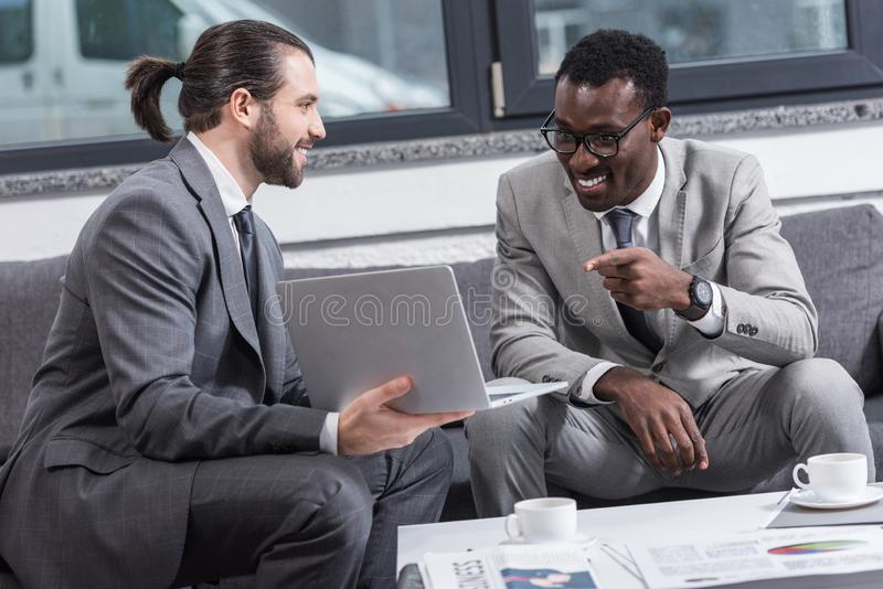 hombre de negocios afroamericano sonriente que se sienta en el sofá y que señala con el finger fotos de archivo libres de regalías