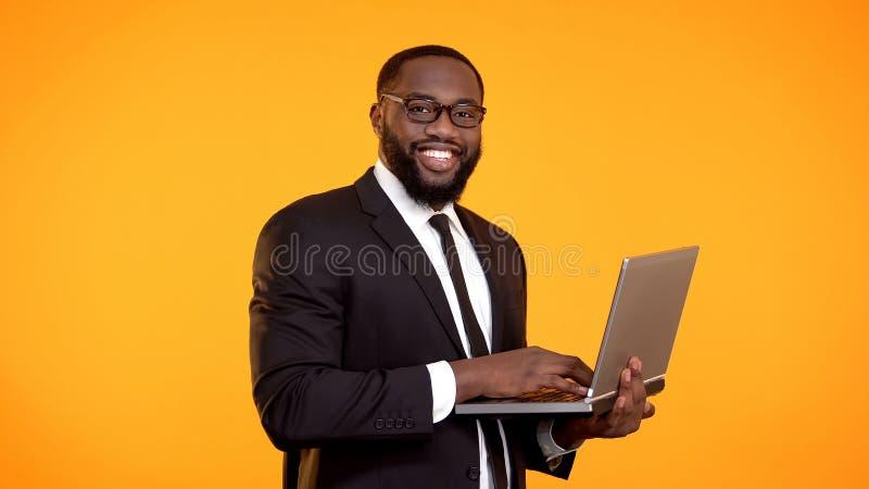Hombre de negocios afroamericano sonriente que trabaja en el ordenador port?til, crecimiento de la carrera, negocio imagen de archivo libre de regalías