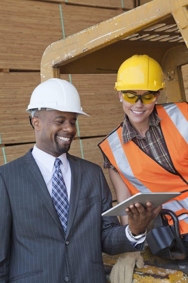 Hombre de negocios afroamericano y trabajador industrial de sexo femenino que miran la PC de la tableta fotos de archivo