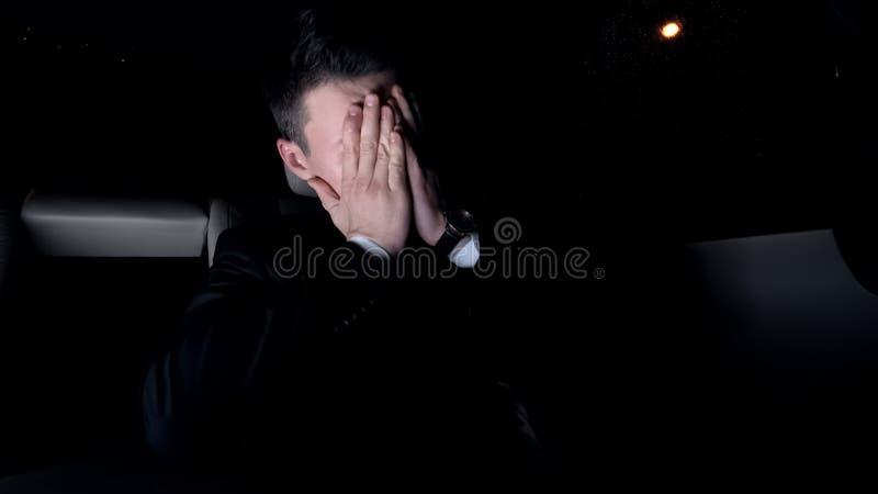 Hombre de negocios agotado que conduce a casa después de la reunión agotadora, problemas del trabajo imagen de archivo libre de regalías