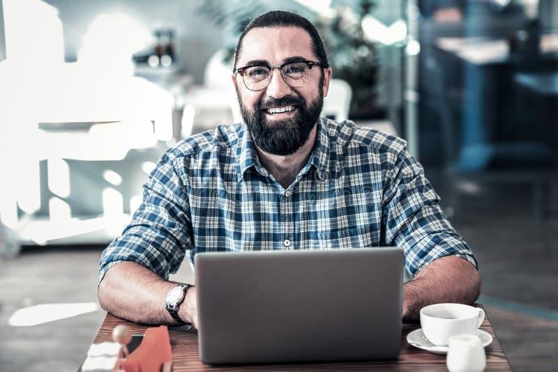 Hombre de negocios agradable sonriente que siente el funcionamiento alegre en el ordenador portátil fotos de archivo libres de regalías