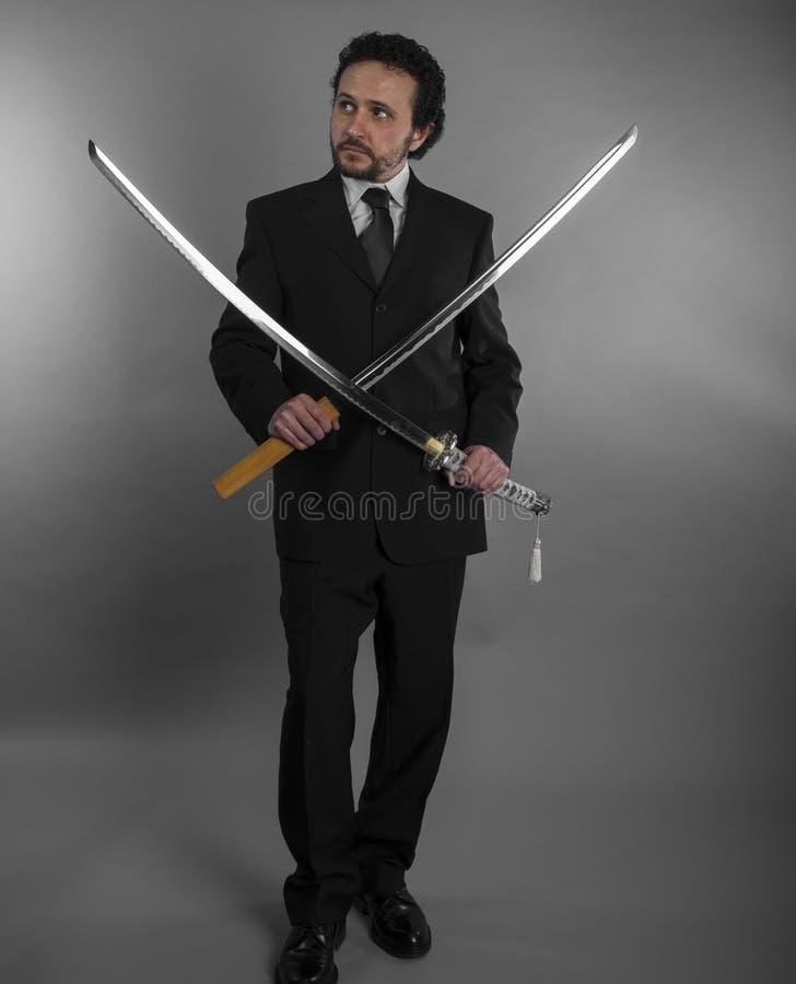 Hombre de negocios agresivo con las espadas japonesas en defensiva y def imagen de archivo