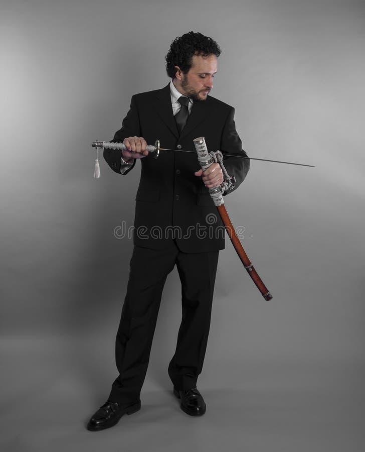 Hombre de negocios agresivo con las espadas japonesas en defensiva y def foto de archivo
