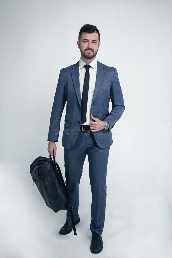 Hombre de negocios aislado en el fondo blanco vestido en el traje que camina a la cámara con el bolso en sus manos foto de archivo