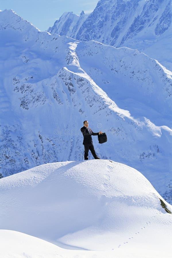 Hombre de negocios al aire libre en la montaña nevosa usando el teléfono imagen de archivo libre de regalías