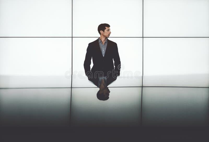 Hombre de negocios al lado de la pared electrónica de pantallas LCD vacías imagenes de archivo