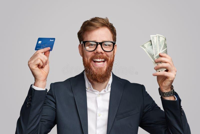Hombre de negocios alegre con la tarjeta del dinero y de banco foto de archivo