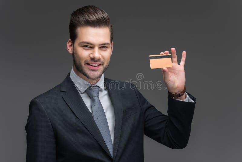 hombre de negocios alegre hermoso que sostiene la tarjeta de crédito de oro, fotos de archivo libres de regalías