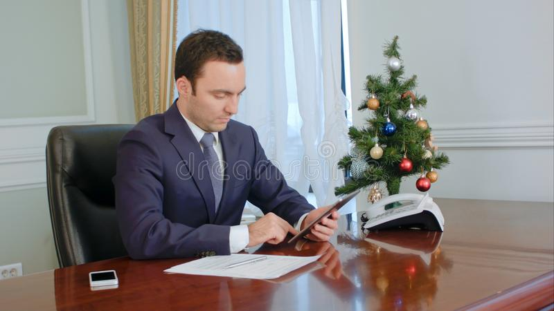 Hombre de negocios alegre joven usando la tableta digital moderna en oficina fotografía de archivo