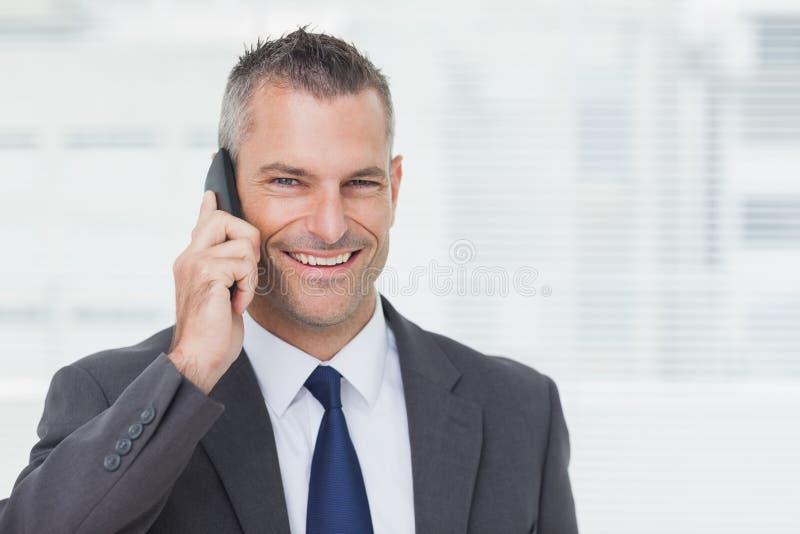 Hombre de negocios alegre que mira la cámara mientras que teniendo una llamada de teléfono fotos de archivo