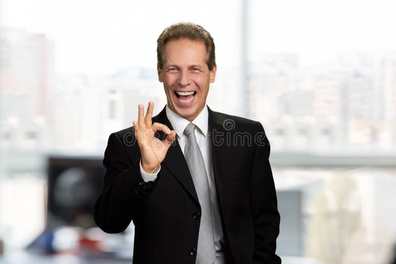 Hombre de negocios alegre que muestra la muestra aceptable imagenes de archivo