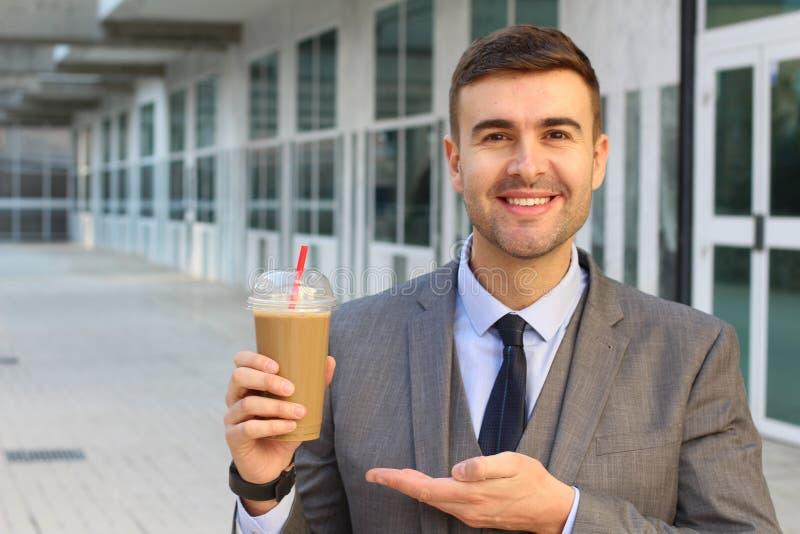 Hombre de negocios alegre que muestra su café imagen de archivo