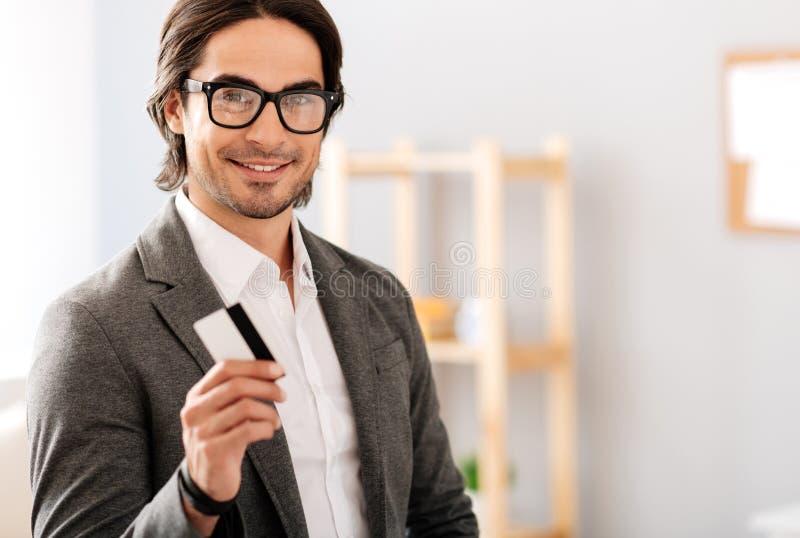 Hombre de negocios alegre que sostiene la tarjeta de crédito fotografía de archivo libre de regalías