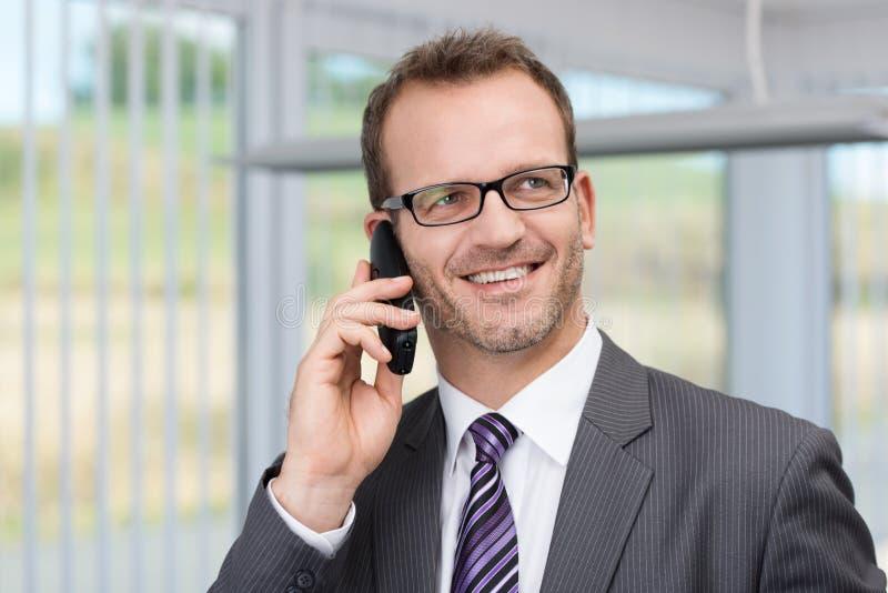 Hombre de negocios alegre que tiene una conversación telefónica foto de archivo