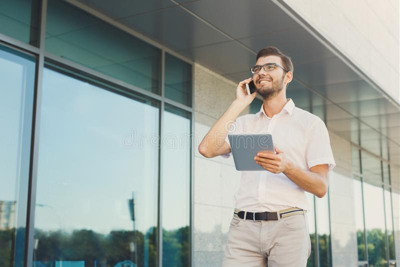 Hombre de negocios alegre usando el teléfono y la tableta al aire libre imagenes de archivo