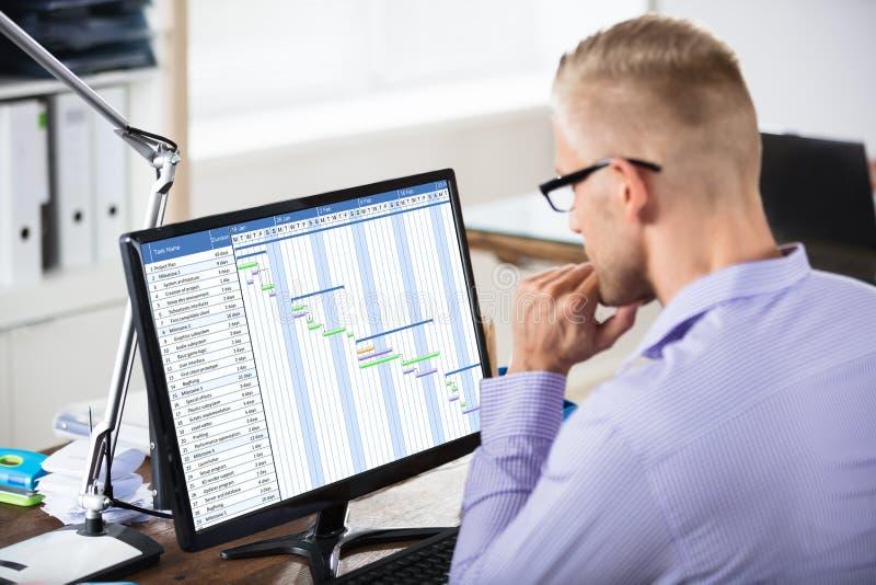 Hombre de negocios Analyzing Gantt Chart en el ordenador imagen de archivo
