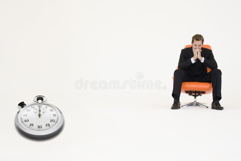 Hombre de negocios ansioso que se sienta en silla con el cronómetro que muestra el tiempo que representa la pérdida de tiempo imagen de archivo libre de regalías