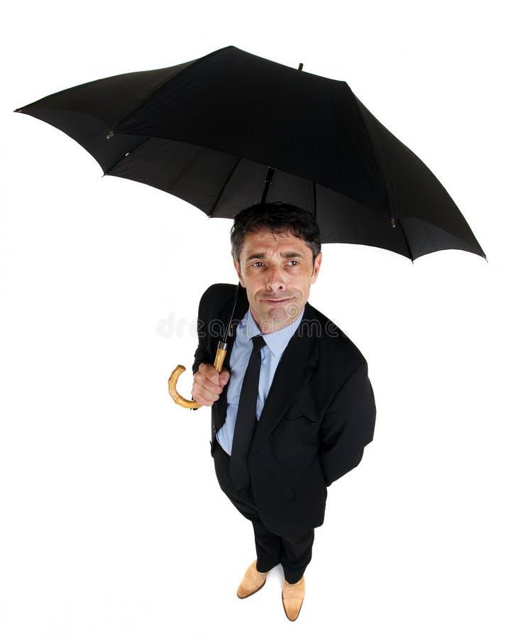 Hombre de negocios apuesto que abriga debajo de un paraguas imagen de archivo