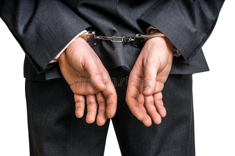 Hombre de negocios arrestado en esposas con las manos detrás detrás fotografía de archivo libre de regalías