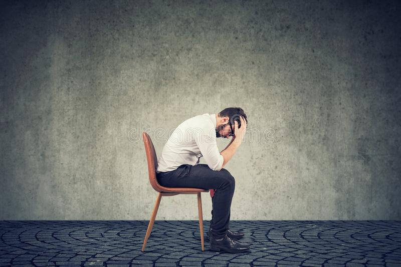 Hombre de negocios arruinado triste que se sienta en una oficina vacía fotos de archivo libres de regalías