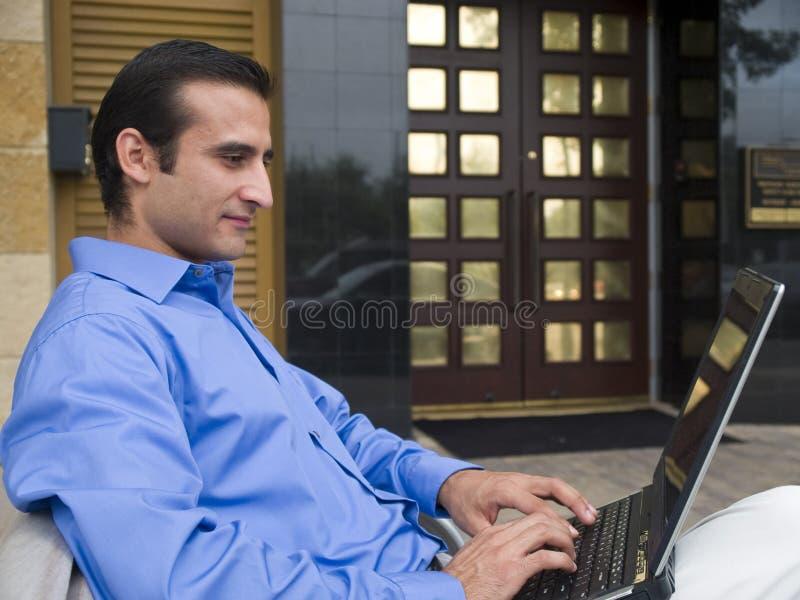 Hombre de negocios asentado con la computadora portátil imagen de archivo