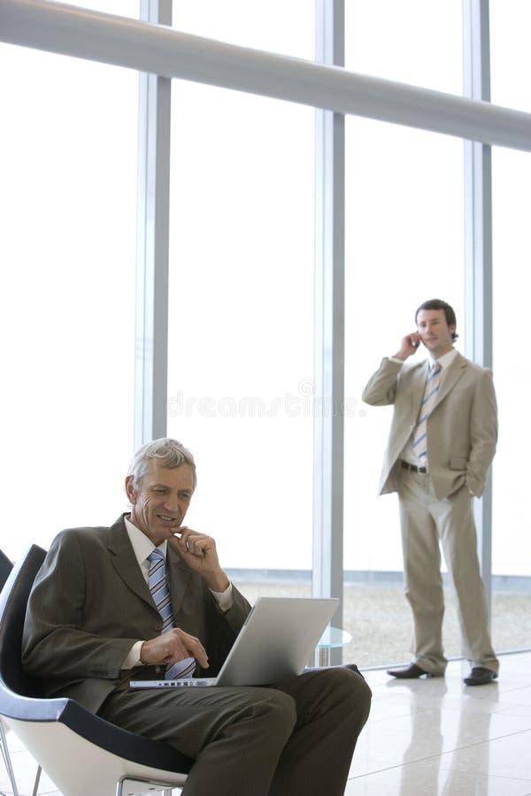 Hombre de negocios asentado con la computadora portátil imagen de archivo libre de regalías