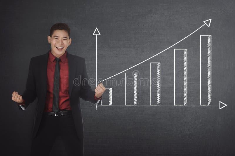 Hombre de negocios asiático acertado que se coloca al lado de gráfico financiero imágenes de archivo libres de regalías