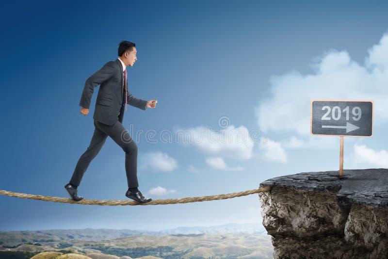 Hombre de negocios asiático atractivo en el puente de cuerda que camina en 2019 imagenes de archivo