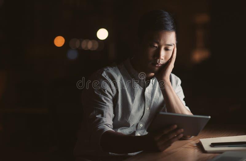 Hombre de negocios asiático cansado usando una tableta en su oficina oscura fotos de archivo libres de regalías