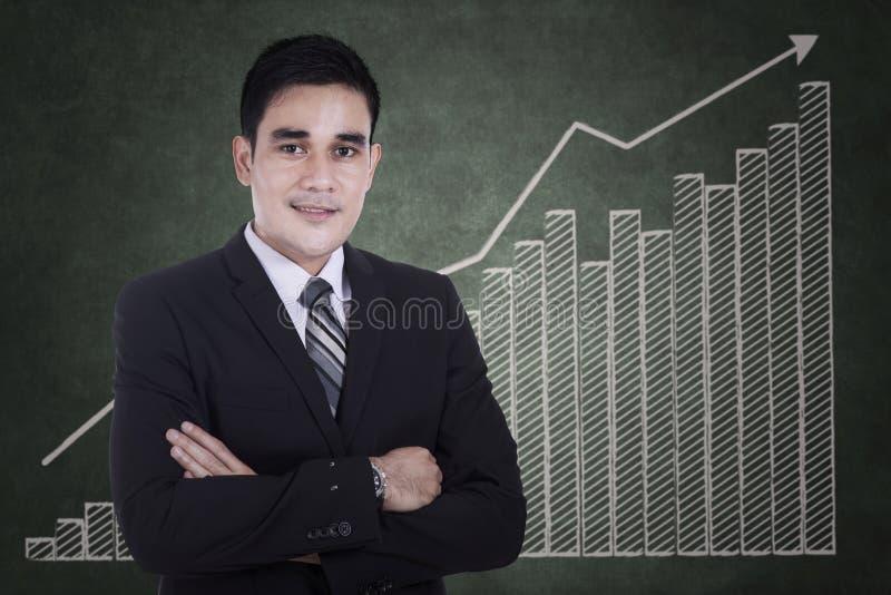 Hombre de negocios asiático con el gráfico cada vez mayor foto de archivo