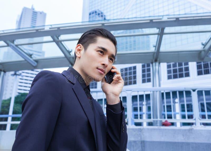 Hombre de negocios asiático con el teléfono elegante fotos de archivo