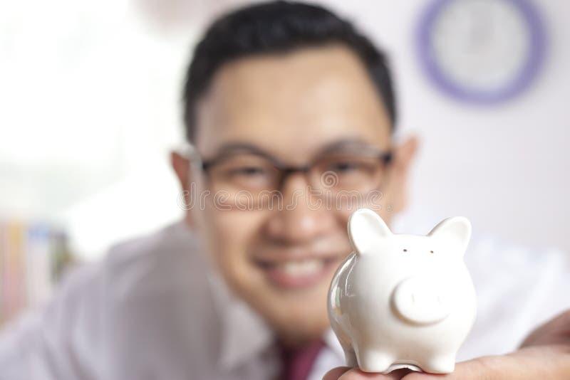 Hombre de negocios asiático con la hucha foto de archivo libre de regalías