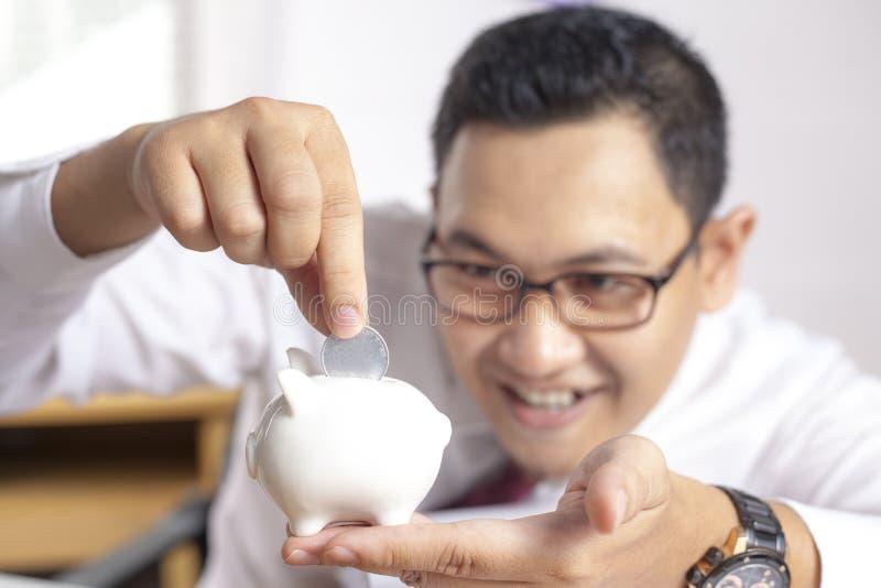 Hombre de negocios asiático con la hucha imagen de archivo libre de regalías