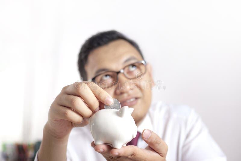 Hombre de negocios asiático con la hucha foto de archivo