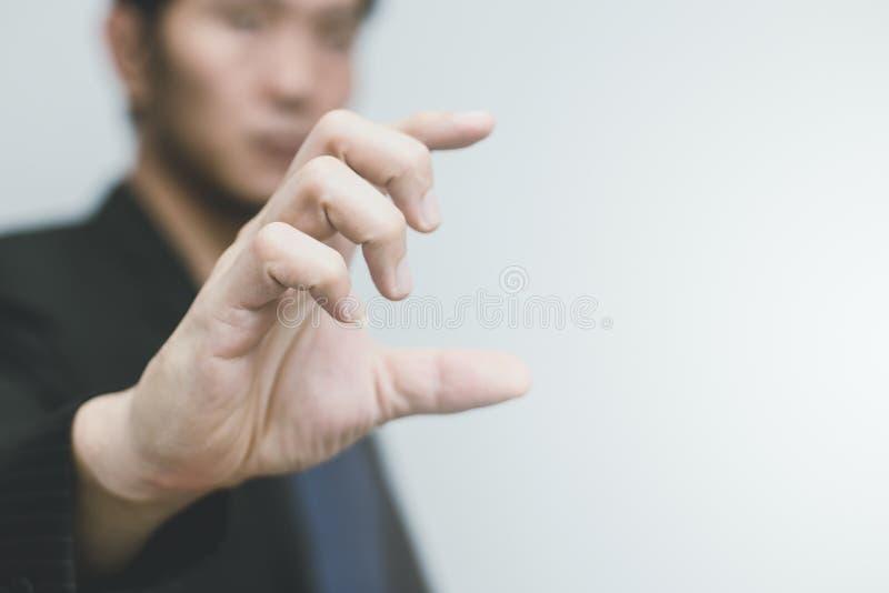 Hombre de negocios asiático con tamaño o la escala de la demostración del finger de la mano fotografía de archivo