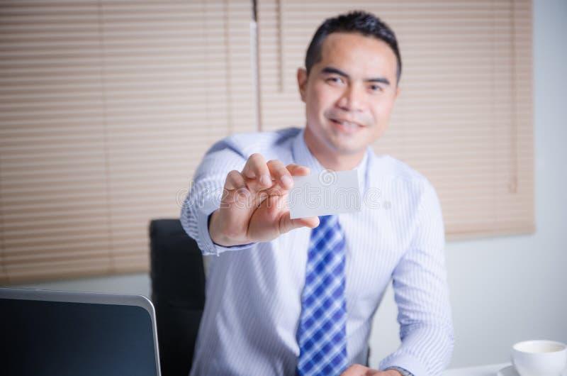 Hombre de negocios asiático de la sonrisa feliz que muestra la tarjeta de visita en blanco w foto de archivo libre de regalías