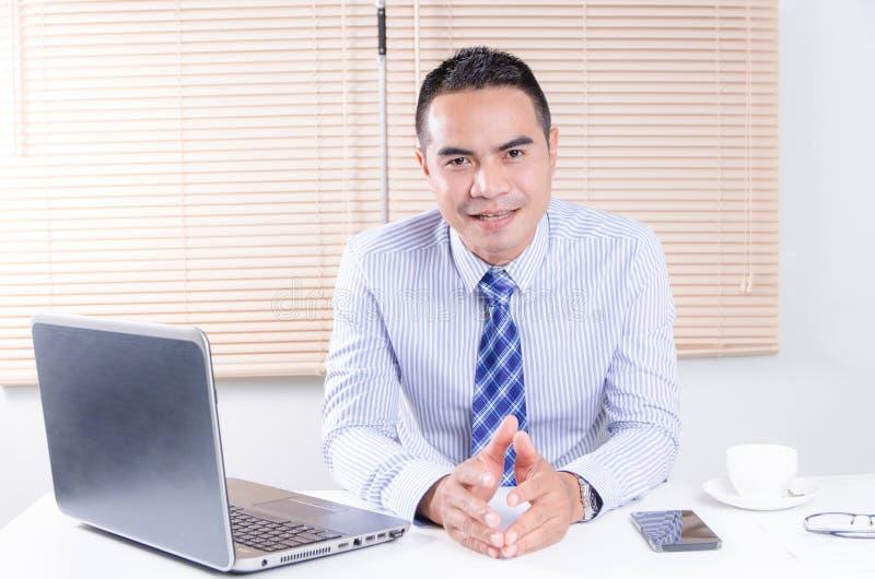 Hombre de negocios asiático de la sonrisa feliz que se sienta en oficina foto de archivo