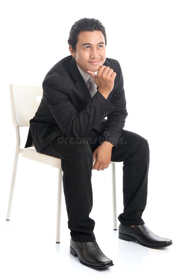 Hombre de negocios asiático del cuerpo completo que se sienta en la silla blanca y el pensamiento foto de archivo