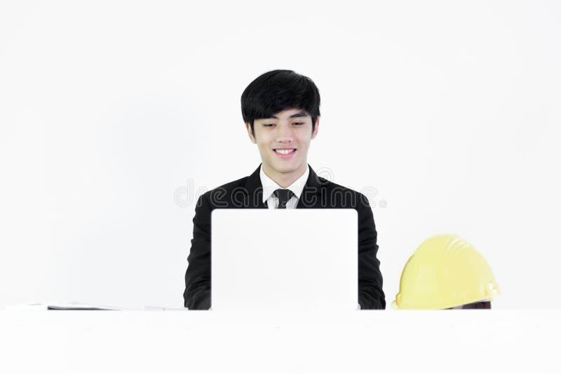 Hombre de negocios asiático del encargado que se sienta en el escritorio y que trabaja con lapto imagenes de archivo