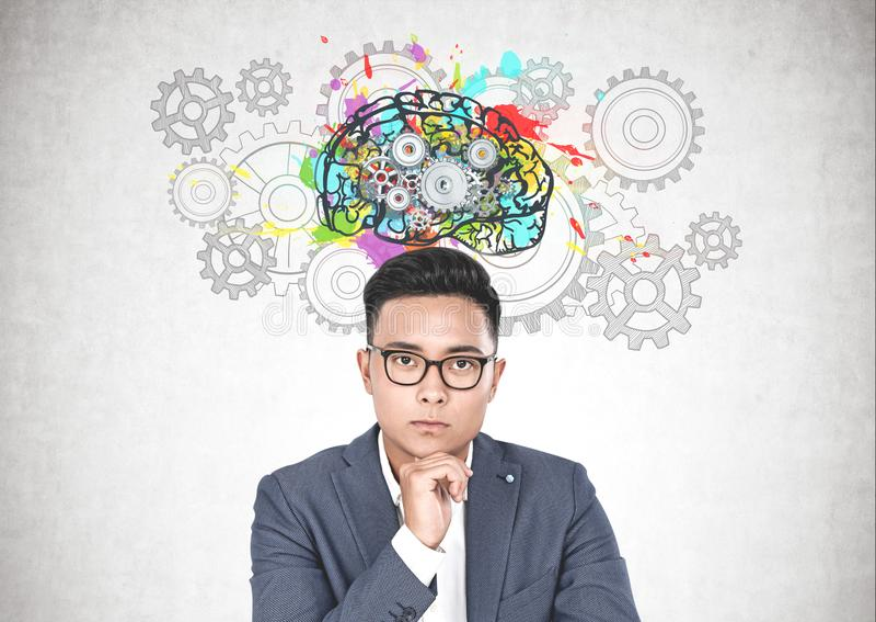 Hombre de negocios asiático en vidrios, cerebro del engranaje fotografía de archivo libre de regalías