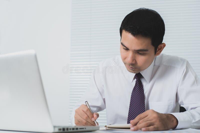 Hombre de negocios asiático hermoso que trabaja seriamente en la oficina fotografía de archivo