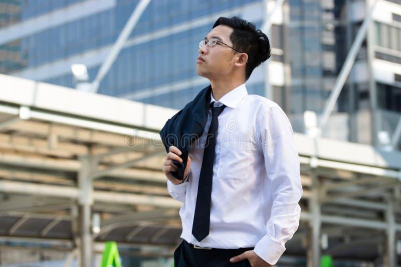 Hombre de negocios asiático joven atractivo en el traje que se coloca y que mira lejos la oficina exterior imagen de archivo