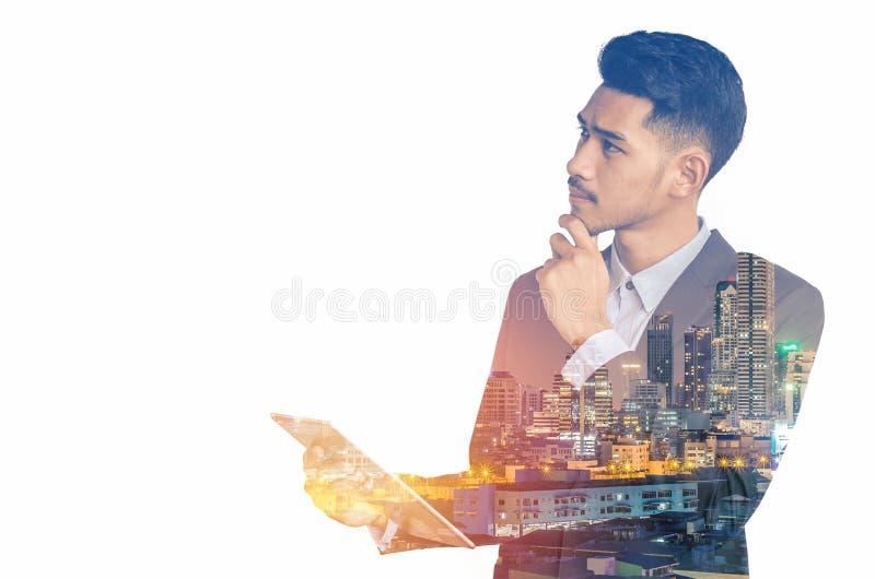 Hombre de negocios asiático joven con la comunicación de la tableta aislada en el fondo blanco foto de archivo