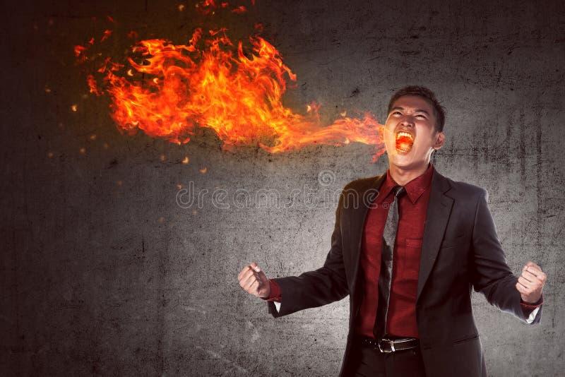 Hombre de negocios asiático joven en la cólera que quema en llama imagen de archivo