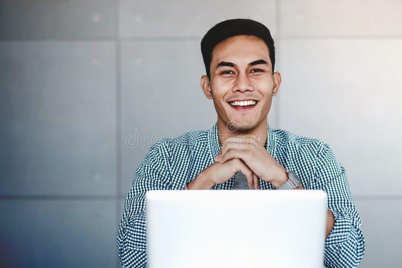 Hombre de negocios asiático joven feliz Working en el ordenador portátil del ordenador fotografía de archivo libre de regalías